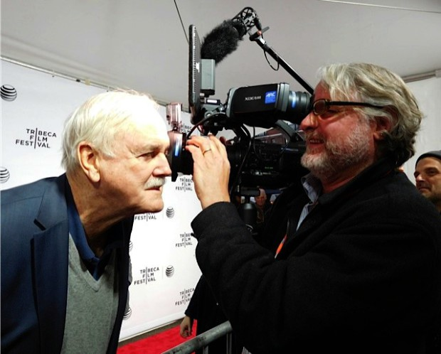 "John Cleese clowns around with a cameraman on the red carpet at the Tribeca Film Festival screening of ""Monty Python and the Holy Grail"" 