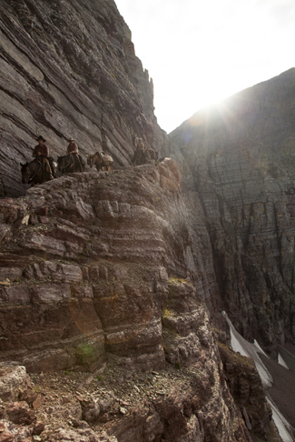 "The men and their horses in ""Unbranded"" travel on a narrow canyon path."