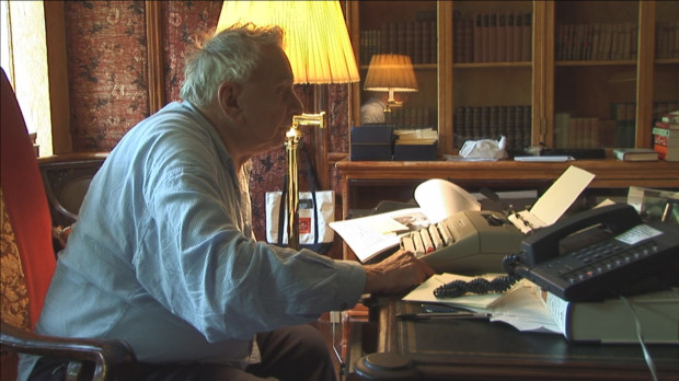 "Gore Vidal in front of the old-fashioned typewriter that he still used for his writings in a still from ""Gore Vidal: The United States of Amnesia."""